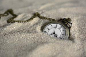砂の中に埋もれた時計の写真