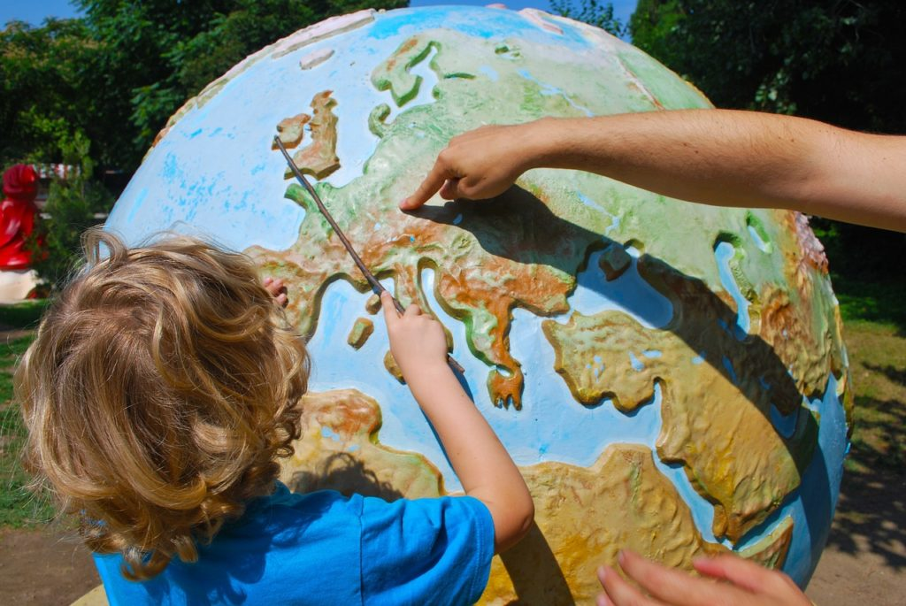 世界地図を指さす男の子