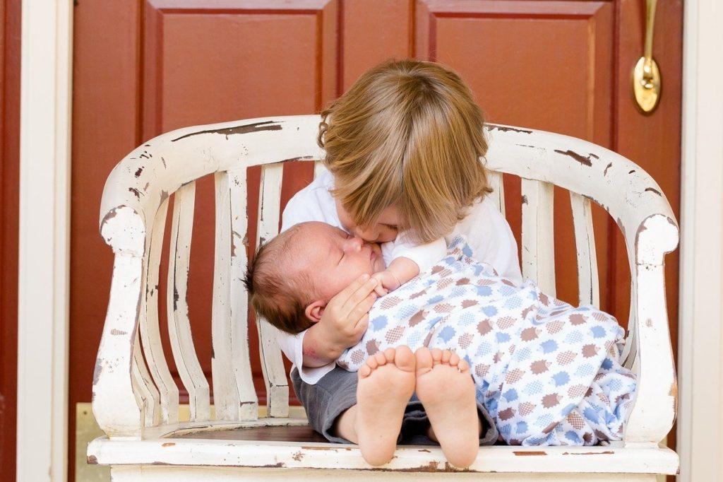 赤ちゃんにキスする男の子の写真