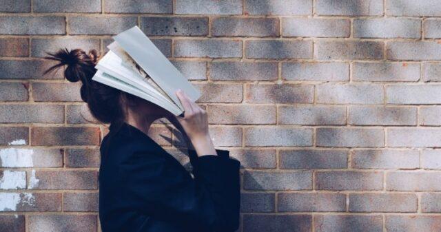本を読み難しさを感じる女性の写真